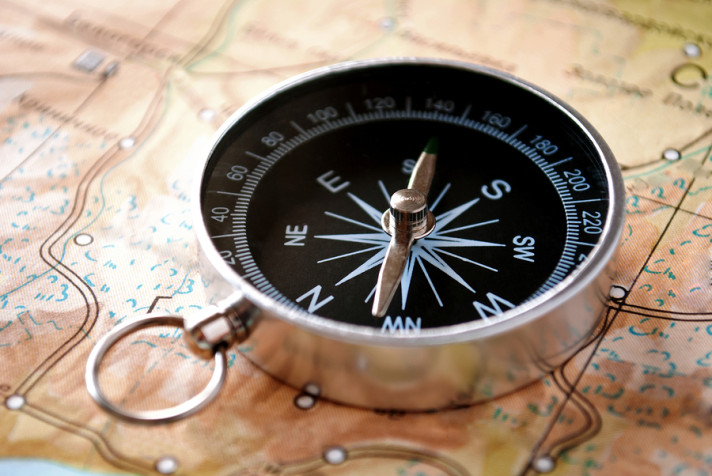 Handheld compass lying on a map showing the needle and cardinal points of north south east and west to aid in magnetic navigation to plot a route or direction to a specific destination